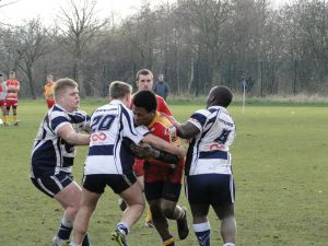 Mancunians' Kemar Giles charging into the tackle.